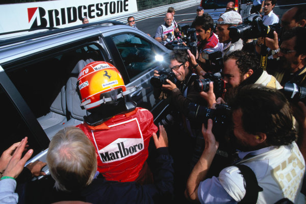 2004 Belgian Grand Prix.Spa Francorchamps, Belgium. 27th - 29th August.Michael Schumacher, Ferrari F2004 climbs into the car to take him to the podium.World Copyright:LAT PhotographicRef:35mm Image A04