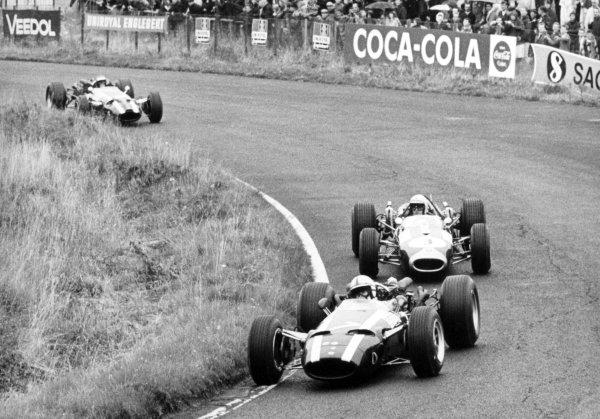 1966 German Grand Prix.Nurburgring, Germany. 7 August 1966.John Surtees, Cooper T81-Maserati, 2nd position, leads Jack Brabham, Brabham BT19-Repco, 1st position, and Jochen Rindt, Cooper T81-Maserati, 3rd position, action.World Copyright: LAT PhotographicRef: Autosport b&w print