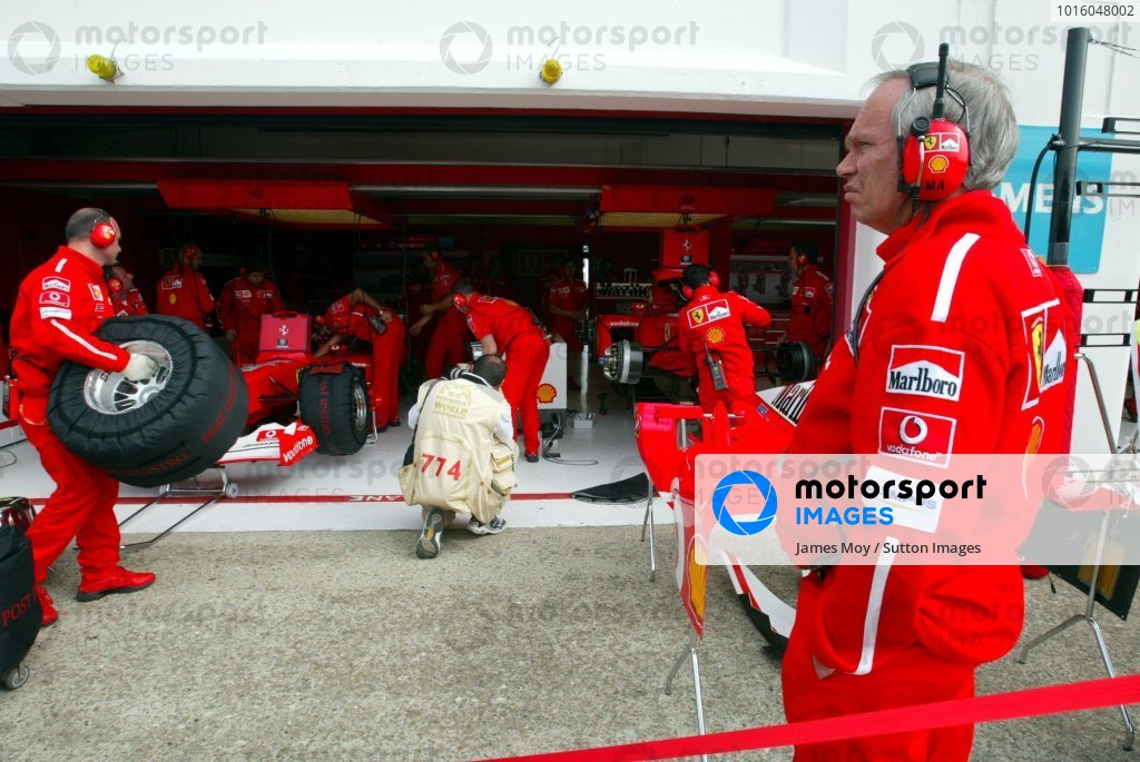 Rory Byrne (RSA) Ferrari Chief Designer oversees work in the Ferrari pit.
