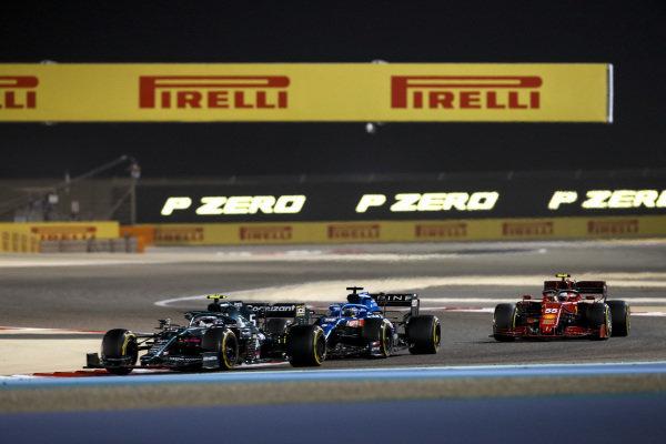 Sebastian Vettel, Aston Martin AMR21, leads Fernando Alonso, Alpine A521, and Carlos Sainz, Ferrari SF21