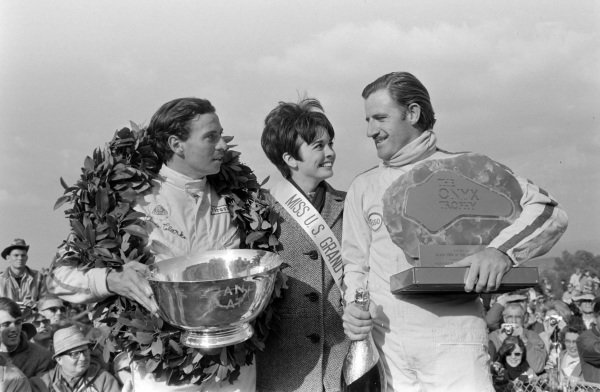 Jim Clark, 1st position, on the podium with his winners' trophy alongside teammate Graham Hill, 2nd position, with his pole position trophy and Miss US Grand Prix.