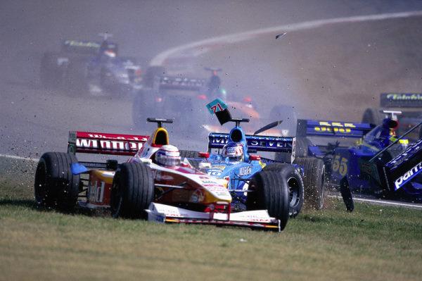 Alex Zanardi, Williams FW21 Supertec, runs wide over the grass as Alex Wurz, Benetton B199 Playlife, crashes out behind him.