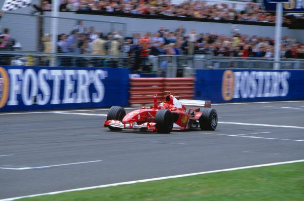 2004 British Grand Prix Silverstone England. 9th - 11th July. Michael Schumacher, Ferrari F2004 crosses the line to take his 80th Grand Prix victory. Action.  World Copyright:Peter Spinney/LAT Photographic  Ref:35mm image A19