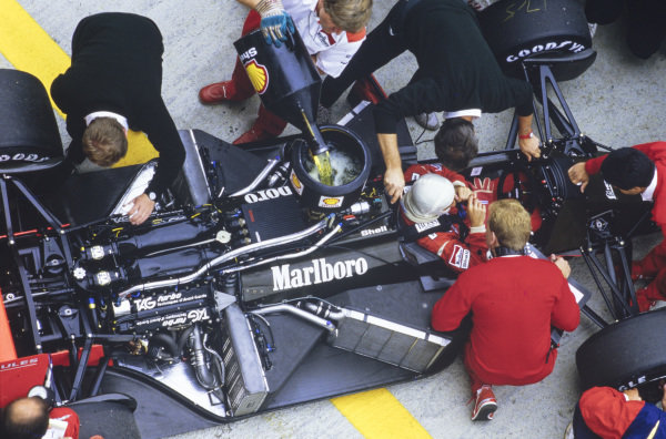 Alain Prost sits in his exposed McLaren MP4-3 TAG as the car is refuelled.