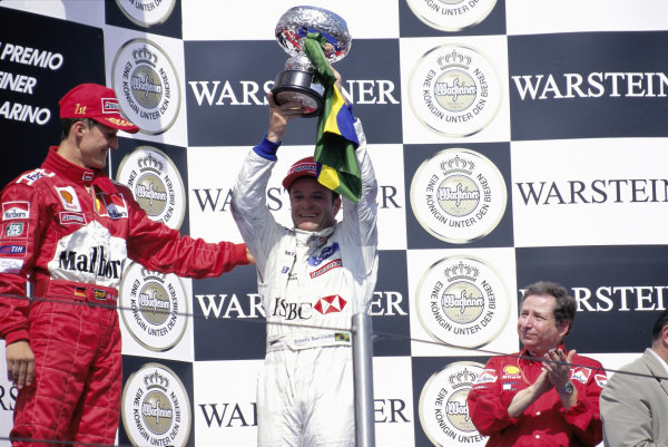 Michael Schumacher, 1st position, congratulates Rubens Barrichello, 3rd position, on the podium alongside Jean Todt.