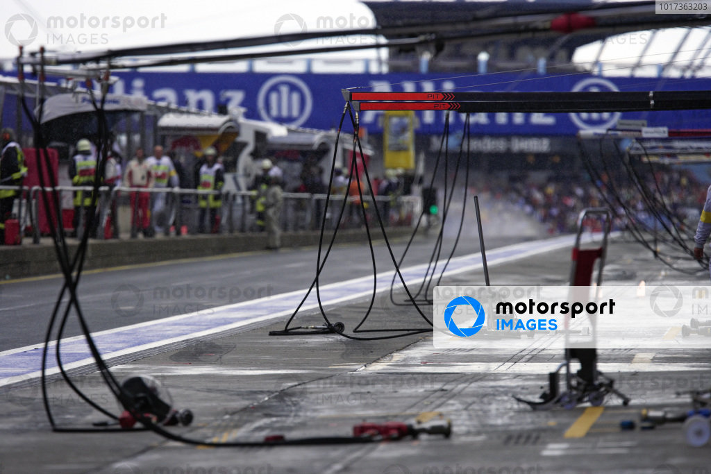 A view down the empty pitlane, wheelguns strewn across the pitboxes as teams wait for the rain to subside.