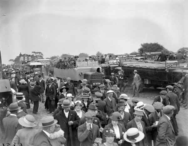 Crowds of spectators arrive at the Epsom Derby, some in a Daimler coach