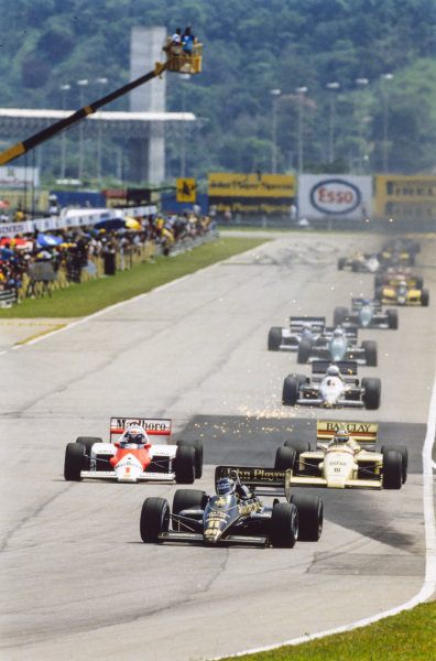 Johnny Dumfries, Lotus 98T Renault, leads Alain Prost, McLaren MP4-2C TAG, Thierry Boutsen, Arrows A8 BMW, a shower of sparks, and Martin Brundle, Tyrrell 014 Renault.