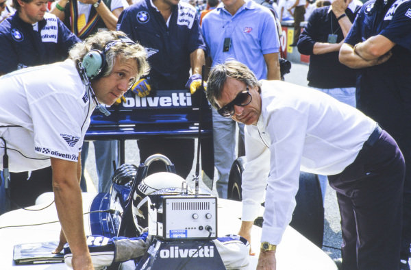 Charlie Whiting and Bernie Ecclestone lean against Riccardo Patrese's Brabham BT55 BMW, as the Italian driver looks at a monitor.