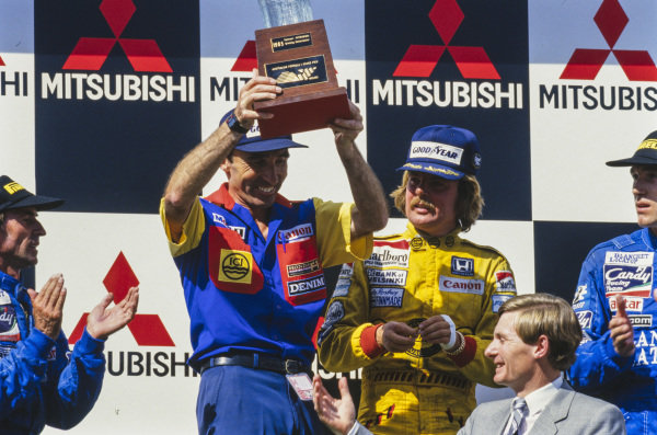 Frank Williams celebrates on the podium as the winning constructor in what would be the final race before his life-changing accident. Beside him is race winner Keke Rosberg, in his final race for the team. The Ligier Renault drivers, Jacques Laffite and Philippe Streiff, are visible.