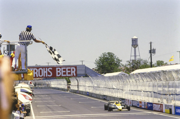 Keke Rosberg, Williams FW09 Honda, takes the chequered flag.