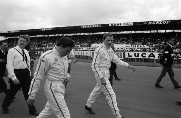 Graham Hill walks with Jim Clark.