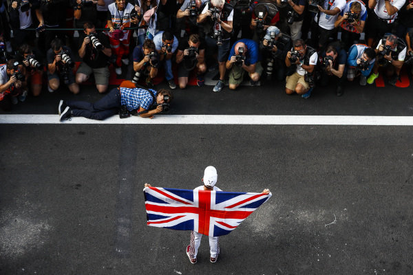 Lewis Hamilton, Mercedes AMG F1, with Union flag draped across his shoulders, celebrates with his team after securing a 5th world drivers championship title