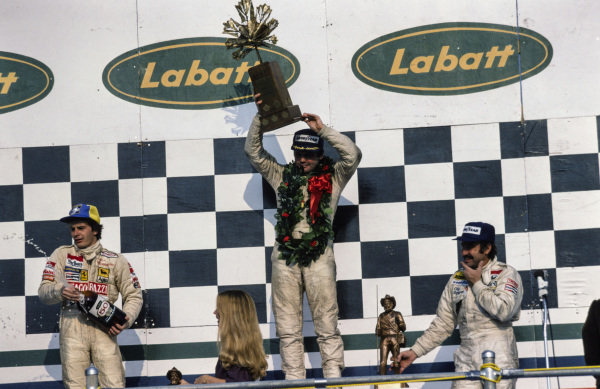 Alan Jones celebrates victory on the podium with Gilles Villeneuve, 2nd position, and teammate Clay Regazzoni, 3rd position.