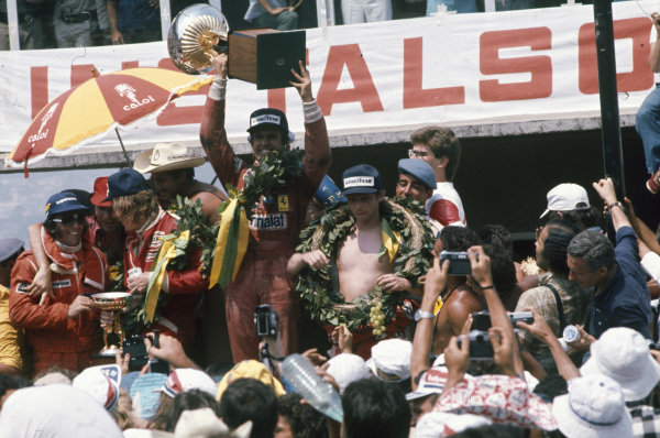Carlos Reutemann celebrates victory on the podium with James Hunt, 2nd position and Niki Lauda, 3rd position. Emerson Fittipaldi can also be seen on the right celebrating his fourth place at his home race.