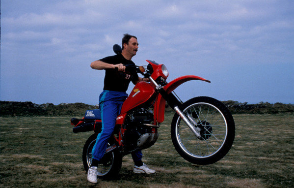 Isle of Man, United Kingdon. 18/4/1989. Nigel Mansell performs a wheelie on a Honda motorcycle at home