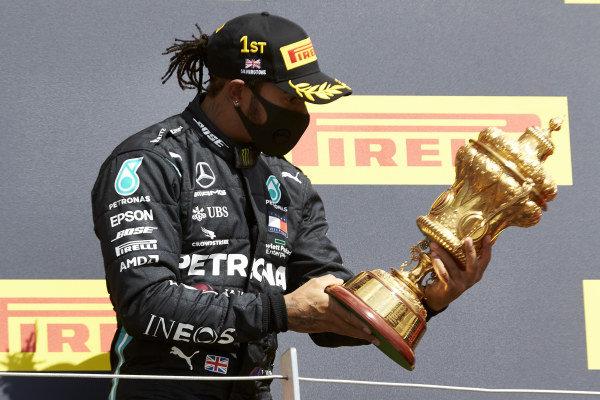 Winner Lewis Hamilton, Mercedes-AMG Petronas F1, celebrates on the podium and holds his trophy