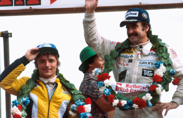 Silverstone, England. 12-14 July 1979. Clay Regazzoni (Williams FW07-Ford), 1st position and Rene Arnoux (Renault RS10), 2nd position, celebrate on the podium. This was Williams Grand Prix Engineering's maiden Grand Prix victory, portrait.  World Copyright: LAT Photographic. Ref:  79GB01