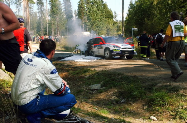 Colin McRae (GBR) watches his Ford Focus RS WRC burn after a loose hyrdaulic cable caught fire.