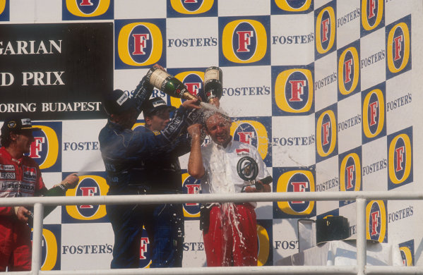 1991 Hungarian Grand Prix.Hungaroring, Budapest, Hungary.9-11 August 1991.Nigel Mansell, 2nd position and Riccardo Patrese 3rd position (both Williams Renault) shower McLaren team boss Ron Dennis with champagne on the podium. Ayrton Senna (McLaren Honda) 1st position also joins in.Ref-91 HUN 01.World Copyright - LAT Photographic