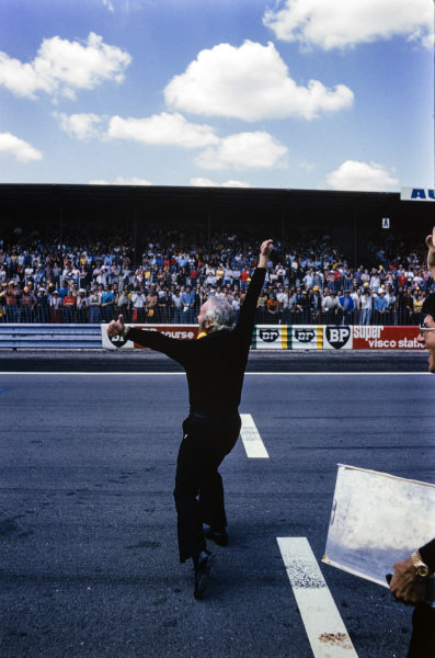 Colin Chapman celebrates Ronnie Peterson's victory at the finish line.