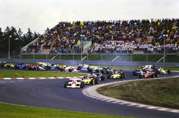 Alain Prost, McLaren MP4-2 TAG, leads Patrick Tambay, Renault RE50, and Nelson Piquet, Brabham BT53 BMW, at the first corner. Further back, Ayrton Senna, Toleman TG184 Hart, makes contact with Keke Rosberg, Williams FW09B Honda, eliminating both.