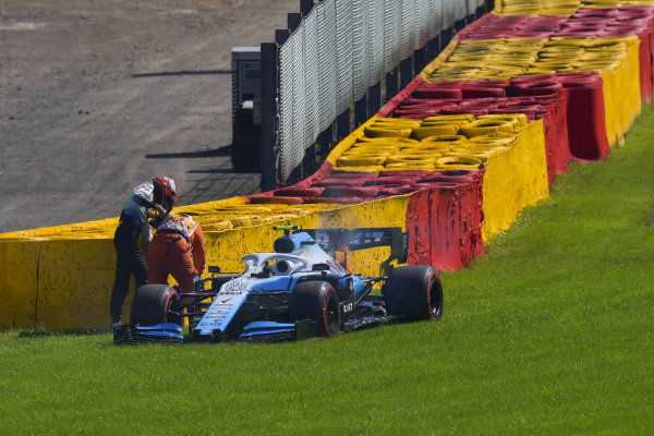 Robert Kubica, Williams Racing, stops in qualifying with a smoking and flaming engine. Kubica helps a marshal extinguish the fire