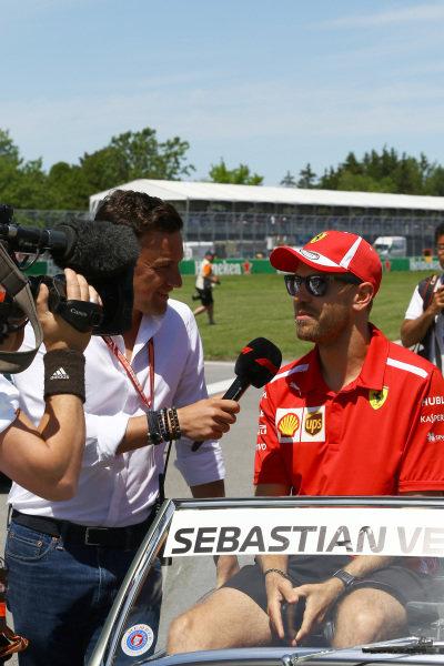 Sebastian Vettel (GER) Ferrari talks with Will Buxton (GBR) FOM TV Presenter on the drivers parade .