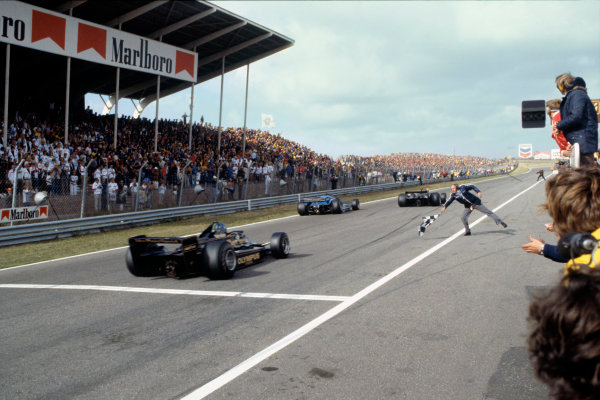 Zandvoort, Holland. 25-27 August 1978. Mario Andretti (Lotus 79-Ford), 1st position, leads Ronnie Peterson (Lotus 79-Ford), 2nd position, across the finish line with Colin Chapman about to throw his hat in the air, action.  World Copyright: LAT Photographic. Ref: 78HOL11