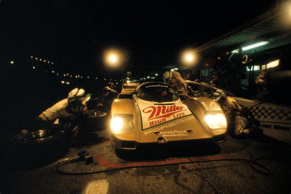 Daytona 24 Hours, Florida, USA. 30th - 31st January 1988. Rd 1. Al Holbert/Derek Bell/Chip Robinson (Porsche 962) takes a night time pit stop. 7th position, action. World Copyright: Bill Murenbeeld/LAT Photographic. Ref: 88IMSA DAY03