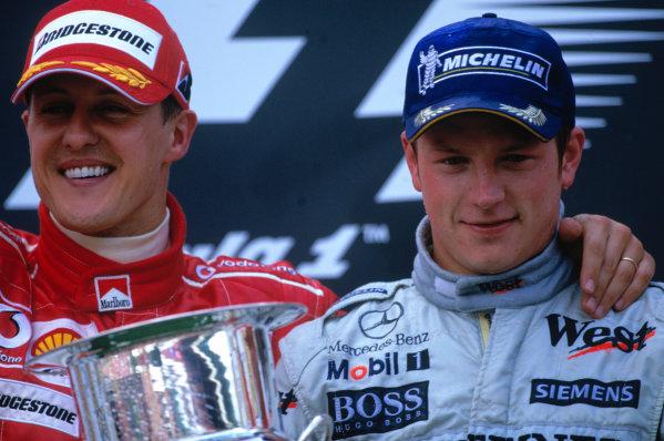 2004 Belgian Grand Prix. Spa Francorchamps, Belgium. 27th - 29th August. Kimi Raikkonen, McLaren Mercedes MP4/19B and Michael Schumacher, Ferrari F2004 celebrate on the podium. World Copyright:LAT Photographic Ref: 35mm Image A21
