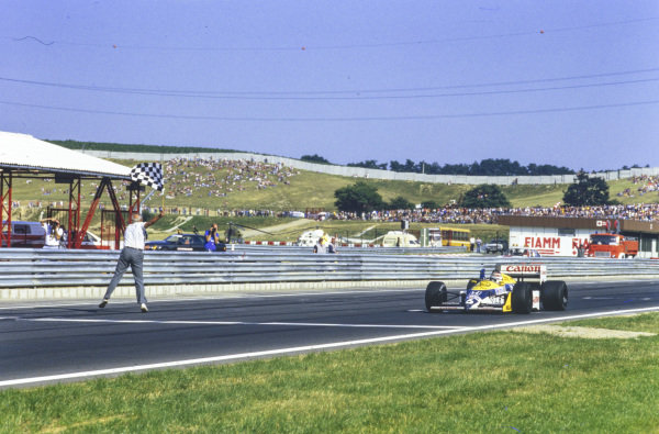 Nelson Piquet, Williams FW11B Honda, takes the chequered flag.