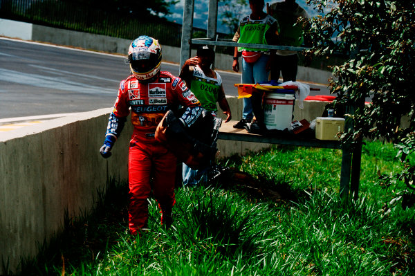 Interlagos, Sao Paulo, Brazil.24-26 March 1995.Rubens Barrichello (Jordan Peugeot) walks back with his seat fitting after he exited the race with a gearbox actuator failure.Ref-95 BRA 05.World Copyright - LAT Photographic