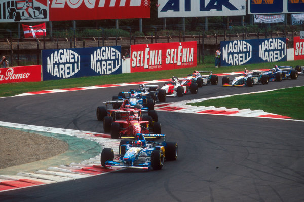 Monza, Italy.8-10 September 1995.Michael Schumacher (Benetton B195 Renault) leads Gerhard Berger, Jean Alesi (both Ferrari 412T2's), Johnny Herbert (Benetton B195 Renault), Damon Hill (Williams FW17 Renault), Mika Hakkinen (McLaren MP4/10B Mercedes), Eddie Irvine, Rubens Barrichello (both Jordan 195 Peugeot's) and Martin Brundle (Ligier JS41 Mugen-Honda) through the Rettifilo Chicane at the start.Ref-95 ITA 06.World Copyright - LAT Photographic