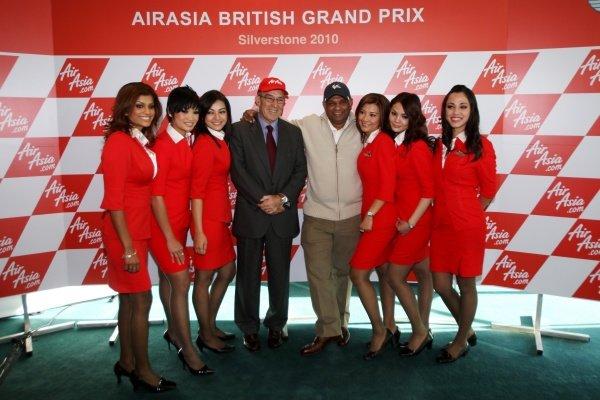 L-R: Carmelo Ezpeleta (ESP) CEO Dorna Sports S.L. and Tony Fernandes (MAL), CEO AirAsia Group, with the AirAsia air hostesses.AirAsia Signs As Title Sponsor for 2010 MotoGP British Grand Prix, Silverstone, England, Wednesday 10 February 2010.