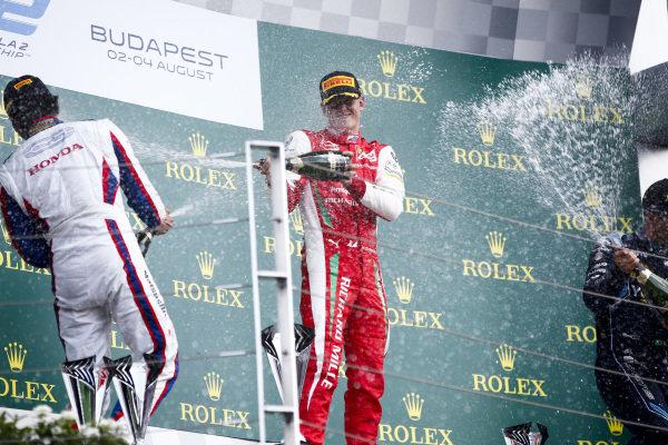 HUNGARORING, HUNGARY - AUGUST 04: Nobuharu Matsushita (JPN, CARLIN), Race winner Mick Schumacher (DEU, PREMA RACING) and Sergio Sette Camara (BRA, DAMS) celebrate on the podium with the champagne during the Hungaroring at Hungaroring on August 04, 2019 in Hungaroring, Hungary. (Photo by Andy Hone / LAT Images / FIA F2 Championship)