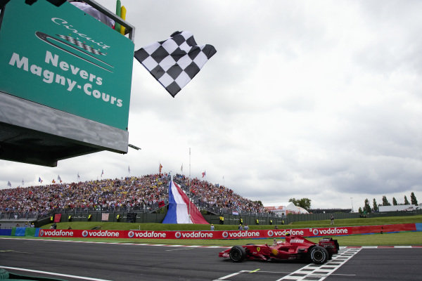 Kimi Räikkönen, Ferrari F2007 raises a fist in celebration as he takes the chequered flag for victory.