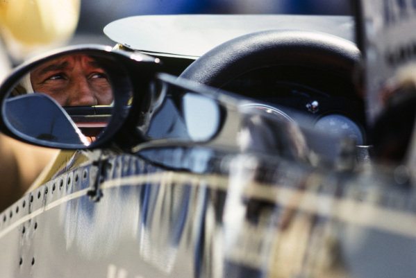 Mario Andretti reflected in the mirror of his Lotus 78 Ford.