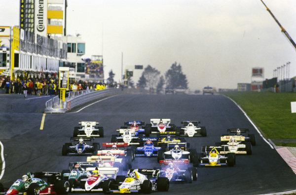 Ayrton Senna, Toleman TG184 Hart, and Keke Rosberg, Williams FW09B Honda, make contact, triggering a multi-car collision.