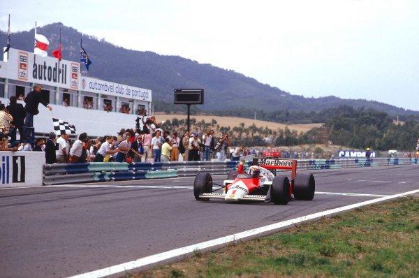 1987 Portuguese Grand Prix.Estoril, Portugal.18-20 September 1987.Alain Prost (McLaren MP4/3 TAG Porsche) takes the chequered flag for 1st position.Ref-87 POR 10.World Copyright - LAT Photographic