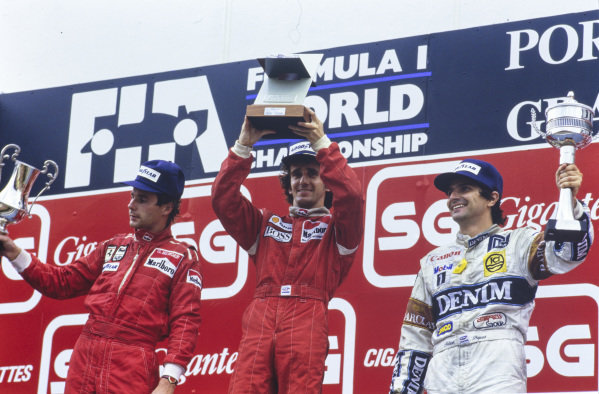 Alain Prost, 1st position, Gerhard Berger, 2nd position, and Nelson Piquet, 3rd position, raise their respective trophies on the podium.