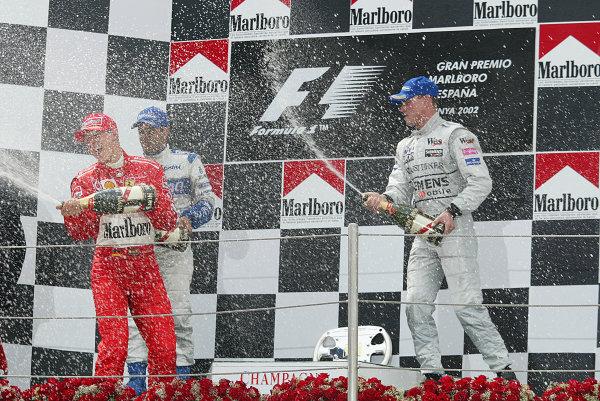 2002 Spanish Grand Prix.Catalunya, Barcelona, Spain. 26-28 April 2002.Champagne celebration on the podium between M. Schumacher, Juan Pablo Montoya and David Coulthard.World Copyright - LAT Photographicref: digital image only