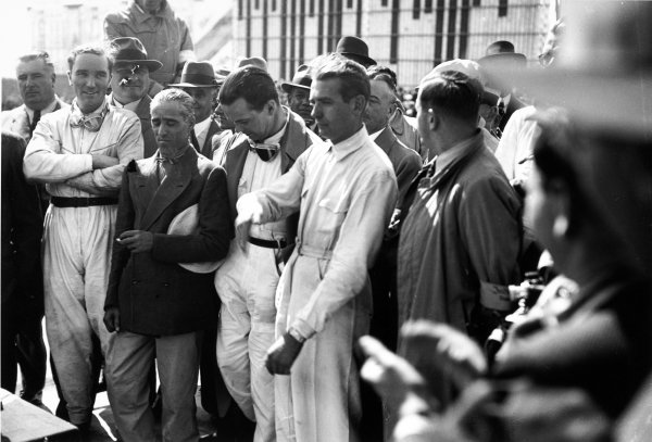 Nurburgring, Germany. 25 July 1937.Tazio Nuvolari, Rudolf Caracciola and other drivers at the pre-race briefing as Korpsfuhrer Huhnlein explained to the drivers that public displaying of affection, i e. kissing your wife or girlfriend on the pitlane was to be considered as non-Aryan behavior, and had to be stopped.World Copyright: Robert Fellowes/LAT PhotographicRef: RF37_GER_30.