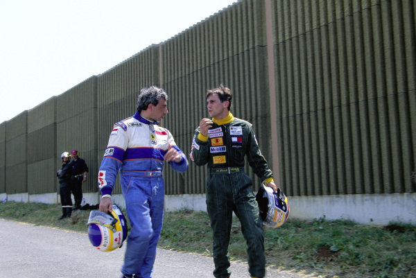 Michele Alboreto and Alex Zanardi walk back to the pits after retiring with engine failures.