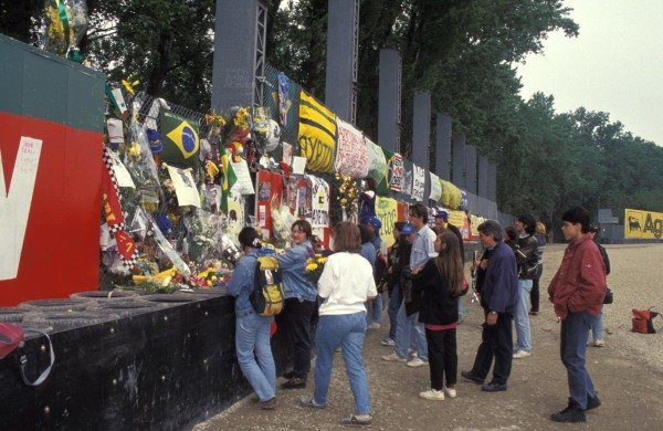 Fans gather and attach flowers and tributes to Ayrton Senna to the fence.