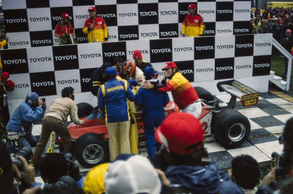Gilles Villeneuve brings his Ferrari 312T4 into victory lane, beneath the podium.