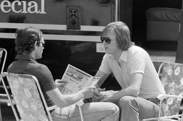 Jacky Ickx, who reads a copy of Autosport magazine, chats with team-mate Ronnie Peterson.