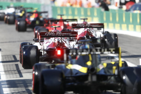 Antonio Giovinazzi, Alfa Romeo Racing C39, leads Daniel Ricciardo, Renault R.S.20, in the pit lane