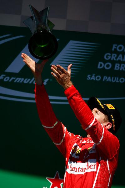 Interlagos, Sao Paulo, Brazil. Sunday 12 November 2017. Sebastian Vettel, Ferrari, 1st Position, celebrates on the podium with his trophy. World Copyright: Andrew Hone/LAT Images  ref: Digital Image _ONZ6878
