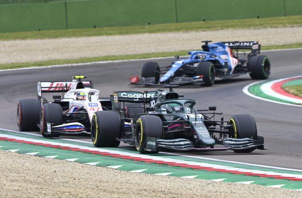 Lance Stroll, Aston Martin AMR21, leads Mick Schumacher, Haas VF-21, and Fernando Alonso, Alpine A521